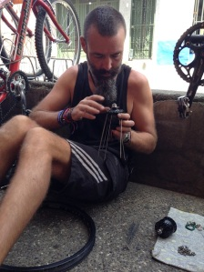 Bren rebuilding the wheel (outside the front of the bike shop) with new SON hub. Thanks